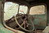 The interior of the driver's cab of an old, abandoned green truck that has been stripped down to the bare minmum.