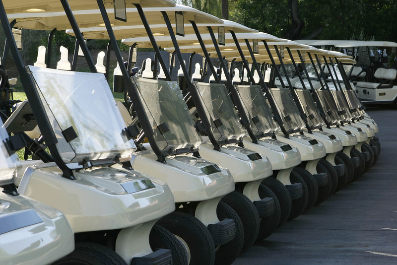 A row of golf carts are lined up at the starting area and are ready to begin the day's round with a shotgun start tournament.
