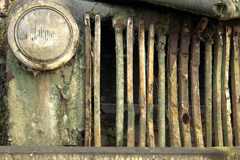 The exterior radiator grill from a old, abandoned and broken-down truck that has rusted out from top to bottom.