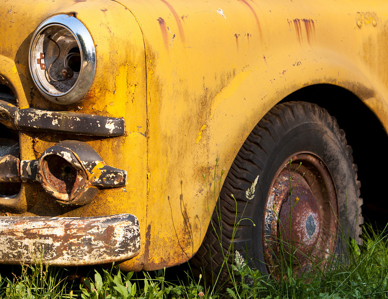 A close up of the front quarter of a historic old yellow farm truck that has been put out to pasture and left to rust in the weather.