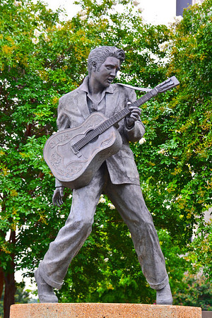 Statue of Elvis    Memphis, Tennessee  In 1980 the world's first bronze Elvis statue was unveiled on Beale Street, where the future King of Rock and Roll crafted his early musical style. But the statue, by Eric Parks, proved too delicate for the elements and souvenir-crazed fans, who stripped its guitar strings and tore the tassels from Elvis's suit. It was taken down in 1994 and moved indoors to the downtown Memphis Tennessee Welcome Center.  That left Elvis Presley Plaza with a big, empty spot. It was finally filled in 1997 with the arrival of a new, completely different bronze Elvis statue by sculptor Andrea Lugar. This Elvis, unlike the original, shows him as he would have looked on Beale Street circa 1955 (pre-tassels), wearing a stage outfit he might have bought at Lansky Bros. down the block.  Although designed to be more sturdy than the previous statue, it's also kept at a distance from the public behind an encircling fence.