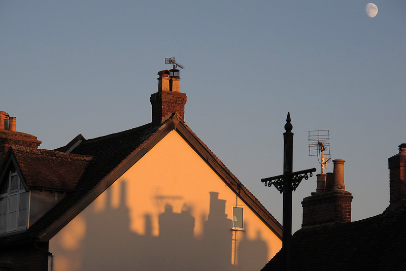Chimneys silhouetted on a blank wall.