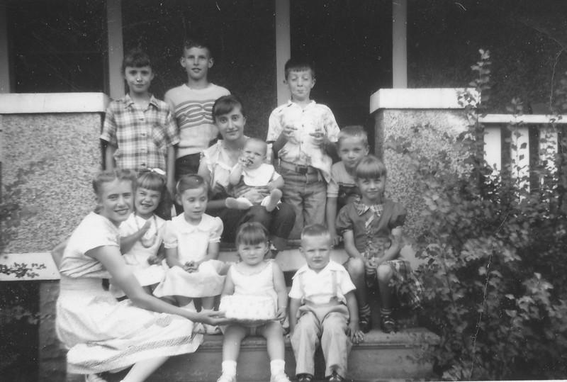 Lisa's 2nd or 3rd birthday<br /> Back row, left to right:  Rose Rita Truempi, Howard Sheehan, Pauline Truempi, (baby Mary Jane Hoskins?),Dicki Johnson?, Billy Hoskins and Mary Kay Sheehan<br /> Front row, left to right: Marie Truempi, Bonnie Hoskins, Mary Johnson?, Lisa Von Arx, and Mike Hoskins.<br /> - on the porch of Lisa's grandparents, Joe and Verna Von Arx.