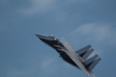 F-15 fighter streaks across the bow of the crane