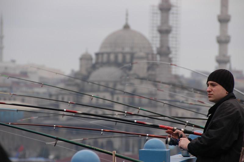 Fisherman on the Galata Bridge across the Golden Horn, Istanbul, Turkey.