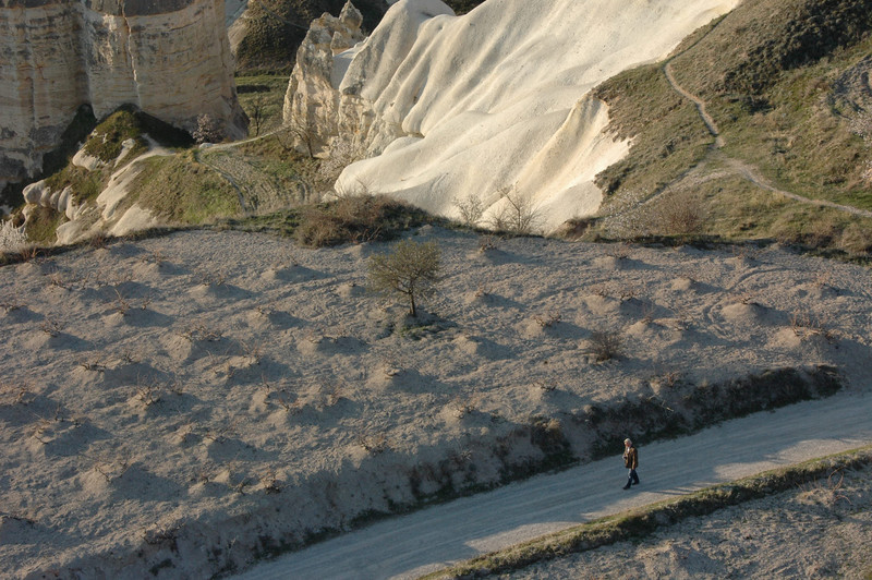 Fallow field and man walking on country lane, Cappadocia, Turkey.