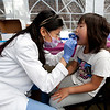 Cindy Chew <br /> 7/23/12<br /> Yu-Hsing Kao, a third year UCSF pediatric dental resident, gives a dental screening to Kumiko Komori at the UCSF School of Dentistry children's free dental screening held during Sunday Streets Family Health and Wellness Fair in the Bayview on Sunday.