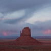The last rays of the setting sun light up the clouds behind one of the Mittens in Monument Valley
