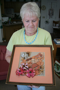"Janet Bandy shows a work of art where the flowers are composed of orange rinds that dried to a porcelain texture. The stones in the image are ""beach bricks"" the rounded remains of bricks that have been worn by the action of the waves and sand. Also in the image are beechnut hulls, pine cones, and shells. photo by Ray Riedel"
