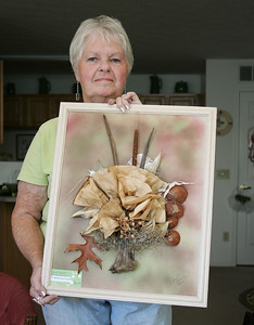 Janet Bandy shows one of her eco art works. The flowers are constructed from used coffee filters. Other components of the image are constructed from driftwood, milkweed pods, spanish moss, jacaranda seeds, hydrangea, and an oak leaf. photo by Ray Riedel