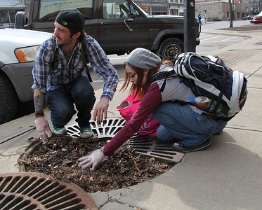 2013_03_10__Sean Nichols and K. Davis cleanup trash from under a grate on Broad Street in Elyria as part of the Elyria Urban Garden Initiative. photo by Ray Riedel