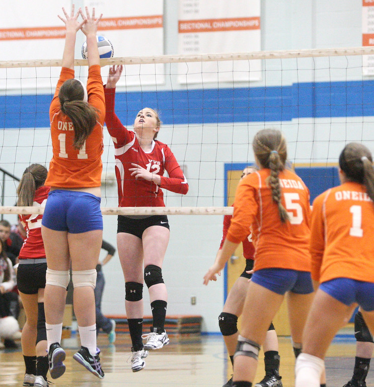 . VVS\' Sydney Keenan (12) puts a shot over the net as  Oneida\'s Matteson Mair (11) defends in the first game of the match at Oneida on Wednesday, Dec. 4, 2013. VVS won the first game 25-18.