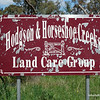 A tattered Hodgson and Horseshoe Creeks land care group sign outside Beechworth, Victoria in October 2013