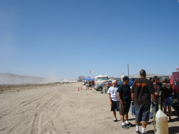 Pic shows track leading into the pit with racers arriving in the distance.  Temps at 100+