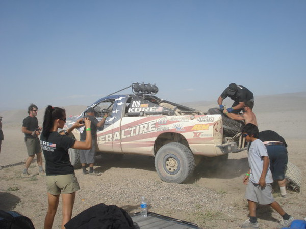 One of the race crews changing a flat tire on a pro truck. Flat and shredded tires was very common.