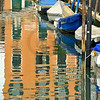 boats line a Venice canal, and a veneian house is reflected in the water