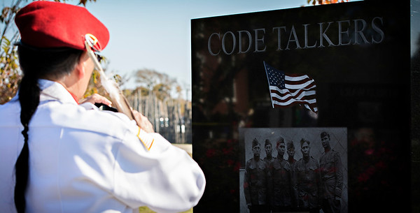Member of the color guard takes a picture of the Code Talker monument.