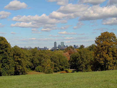 Boston skyline as seen from Larz Anderson Park, Brookline, MA.  The clouds are nicely balanced with blue sky as sunlight plays with the Prudential and other skyscrapers.