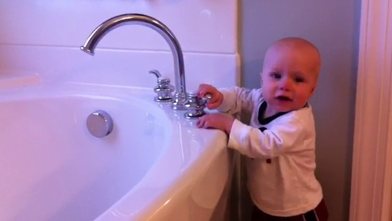 Patrick, 10-months, plays with the faucet.  (Don't worry... I taught him all about water conservation as soon as I stopped recording.)