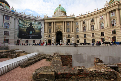 In the foreground are roman ruins, above is the Hofburg.