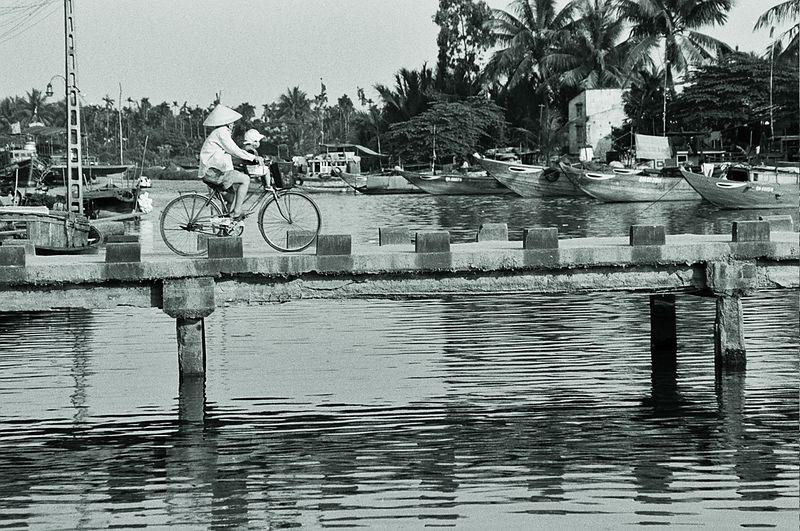 mother and baby on bike on bridge