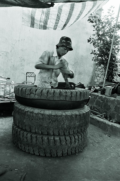 young boy cutting up tyres 2