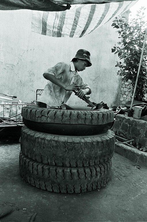 young boy cutting up tyres 1