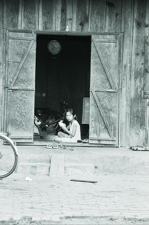young girl eating in doorway