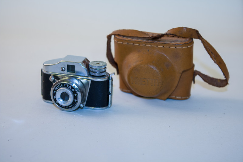 """Minetta The Minetta is a '<em>HIT</em> type' <a href=""""http://en.wikipedia.org/wiki/Subminiature_photography"""">subminiature</a> camera, made in Japan around 1960. As with its cousins (<em>the Minetta Camera and the Minetta Foreign</em>), it takes 17.5mm film. According to the Mike Parker's excellent book '<a href=""""http://www.amazon.com/gp/redirect.html?ie=UTF8&location=http%3A%2F%2Fwww.amazon.com%2FHit-Project-Reference-Classic-Japanese%2Fdp%2F097488880X&tag=cameraderie-20&linkCode=ur2&camp=1789&creative=9325"""">The Hit Project</a><img src=""""http://www.assoc-amazon.com/e/ir?t=cameraderie-20&l=ur2&o=1"""" width=""""1"""" height=""""1"""" border=""""0"""" alt="""""""" style=""""border:none !important; margin:0px !important;"""" />', the Minettas are all classified as QP-style cameras. If anyone has a QP camera for sale, I'd love to add it to the collection.  Other than that, not a lot is known about them. If you can shed some light on any aspect of this wonderful camera, let me know. In the meantime, here are a few relevant resources that may be of interest : <ul> <li><a href=""""http://www.subclub.org/"""">Sub Club</a> : a photographic club for the use and collection of subminiature cameras</li> <li><a href=""""http://www.submin.com/17.5mm/index.htm"""">Submin</a> : this is a great collection of these 'HIT type' subminiature cameras</li> </ul>"""