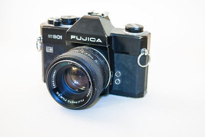 Fujica ST801 The Japanese made Fujica series began with the ST701 in 1971, followed a year later by the ST801 (although mine was manufactured in 1973). It is a fixed pentaprism SLR, uses LED metering (sort of a match needle enhancement) and has shutter speeds up to 1/2000th sec, plus Bulb. The camera I have was first purchased for 120 pounds, has a EBC Fujinon 55mm f1.8 lens, is nice and heavy and takes 35mm film.