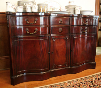 Immaculate serpentine front mahogany sideboard with custom glass top.  Show room shine!