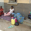 Pregnant mother lying on the varandah of the maternity ward, her laggage next to her, there is no more space in the ward. She is waiting for someone to be discharged before she can be get space.