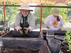 Linda affectionately hugs ball of soil from her compost bin (left rear).