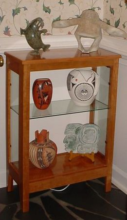 Foyer cherry cabinet w/ art objects - back panel painted white; glass sides/shelf + top lighted.
