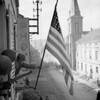 "Infantrymen of 100th Division raise flag above Bitche, Lorraine, France, March 1945.<br /> <br /> ""Among the first to enter Bitche was E Company's commander, Capt. Thomas H. Garahan, who went to the top floor of one of the taller buildings.  Leaning out a window, he proudly displayed the first American flag to fly over the conquered city.  The banner had not been supplied by the division's quartermasters but had been hand-sewn during the three months the city was under siege by Maria Oblinger, proprietress of a popular inn closed down by German occupiers.  Fiercely loyal to the Allied cause, she had crafted the flag while huddling with her family in the stone-arched cellar of the inn, Auberge de Strasbourg, during the city's seemingly interminable shelling.   Working by the light of safety lamps and compelled to hide the flag, she risked arrest and deportation to a concentration camp had her handiwork been discovered"".  - Edward G.Longacre, ""War In The Ruins"", page 209."