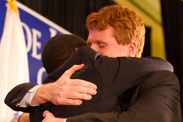 November 6 2012 - Newly elected Representative Joe Kennedy of Massachusetts embraces Mayor Setti Warren of Newton MA, as he enters the stage to give his victory speech at the Newton Marriot on Tuesday night. Photo by Alexa Gonzalez Wagner.