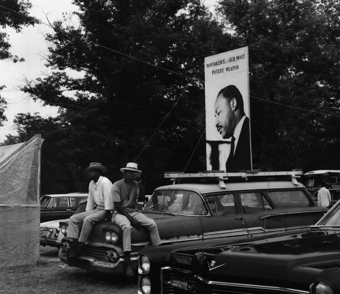 Hope is assassinated in 1968. Dr. Martin Luther King is murdered in April, and Bobby Kennedy is shot down in early June. The Poor People's Campaign takes place between the two killings. Next to their shanty, these men sit on their rusty old car with a billboard of King urging nonviolence attached to the top. The campaign grinds to a to an unsatisfactory halt in the muggy summer and the deprived people go home just as poor