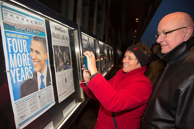 Nina Trasoff and Rodney Jilg of Tucson AZ are among the many pedestrians to stop to read the news about  President Obama's re-election in front of the Newseum in Washington D.C. on November 7, 2012. Front pages are displayed outside the Newseum on Pennsylvania Avenue, one from every state and the District of Columbia as well as a sampling of international newspapers. (Photo by Jeff Malet)
