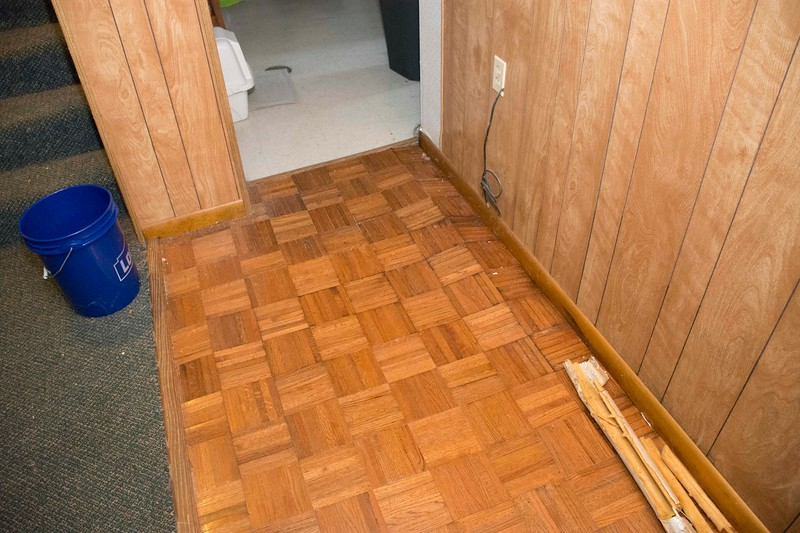 Buckled floor next to garage. Water has seeped underneath.