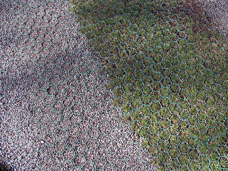A strong plastic grid filled with grass and gravel is both permeable and strong enough to support heavy vehicles.