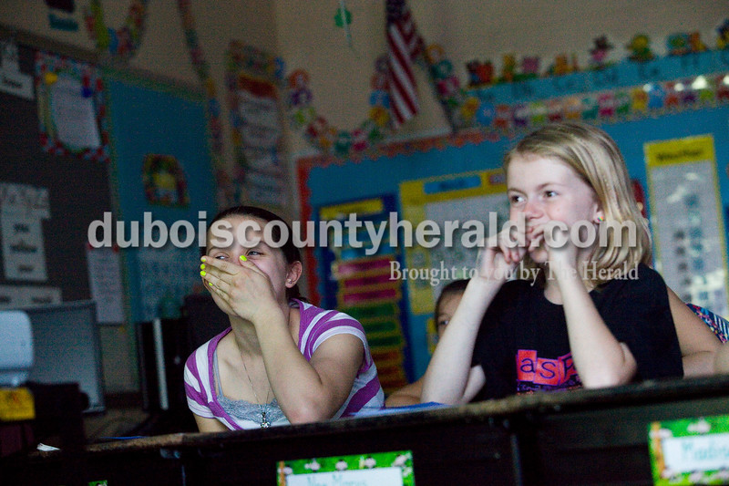 """Laurel Hubster, left, 11, and Olivia Smith, 10, both of Jasper, watched a presentation on international sports during a Multicultural Evening sponsored by Fifth Street and Tenth Street Elementary Schools Tuesday night. Students who participated went to different rooms at Fifth Street Elementary with themes such as international sports and flag identification where they received stickers for their event """"passports."""" The event also had ethnic foods, music and reading by Jasper High School students. Brooke Stevens/The Herald"""