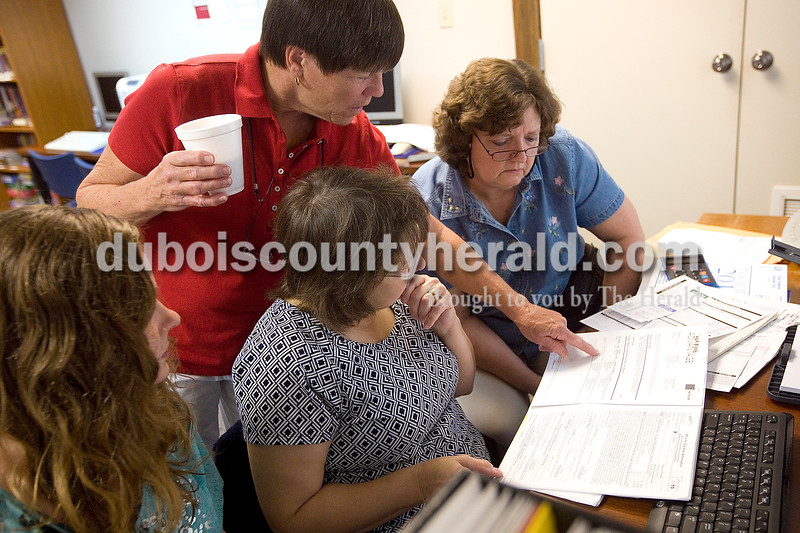 Dave Weatherwax/The Herald<br /> Jayne Hudson of Jasper and a volunteer who helps seniors prepare their taxes at the Arnold F. Habig Community Center, top left, helped Vincennes University Jaspe Campus students Jennifer Hasenour of Dubois, left, and Kelli Curtis of Jasper, middle, as they assisted Rita Reller of Holland and her husband, Jerry, prepare their taxes Tuesday morning at the community center.