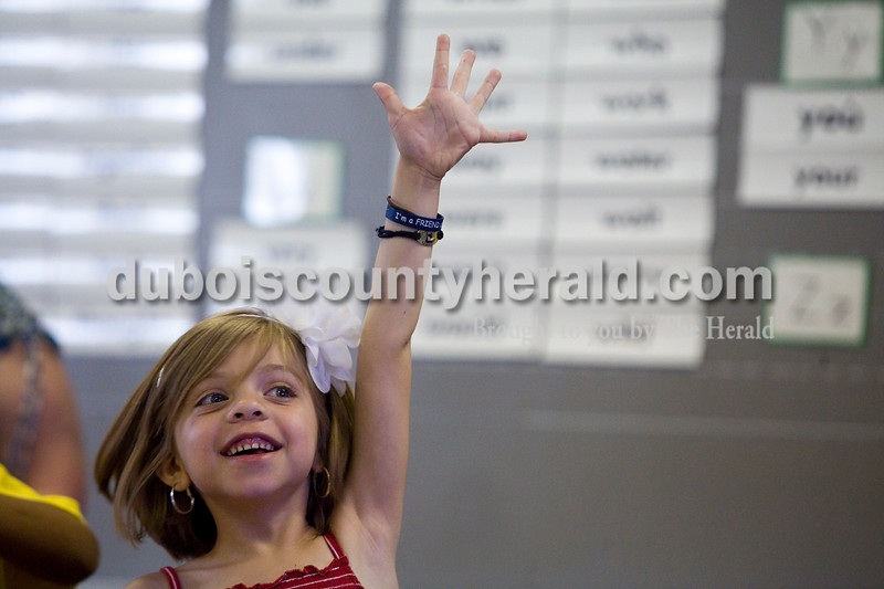 """Gabriela Schmitt of Jasper, 6, rasied her hand during a presentation on country flags during a Multicultural Evening sponsored by Fifth Street and Tenth Street Elementary Schools Tuesday night. Students who participated went to different rooms at Fifth Street Elementary with themes such as international sports and flag identification where they received stickers for their event """"passports."""" The event also had ethnic foods, music and reading by Jasper High School students. Brooke Stevens/The Herald"""