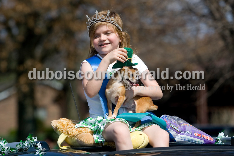 Jounir Miss Labor Day Sydney Davis of Otwell, 10, rode on the top of a car with her dog peanut during the St. Patrick's Celebration Parade Sunday afternoon in Ireland.