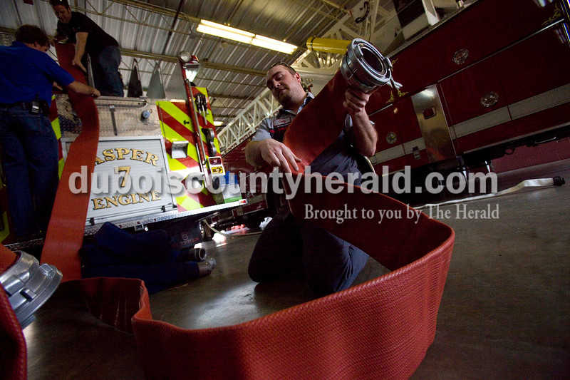 Volunteer Fireman Cody Schmitt of Jasper unraveled a hose to place on the new pumper fire truck the Jasper Fire Department received Tuesday afternoon. The new addition was ordered in July from the Sutphen Corporation and was customized to meet the departments specifications. Brooke Stevens/The Herald