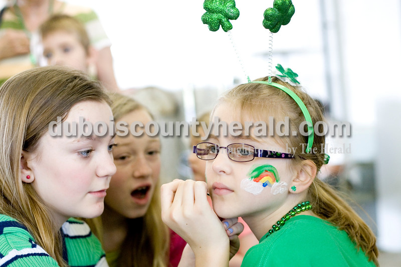 Abby Bunting, left, 12, painted the face of Brianna Williams, 7, both of Jasper, while Averie Himsel of Ireland, 12, watched to learn how to draw a shamrock Saturday morning at the Ireland Fire Department. Brooke Stevens/The Herald