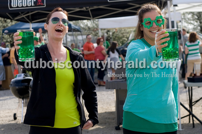 Jamie Peters, left, and Tina Vaal, both of Jasper, competed in the Toast to the O' Blarney Drop Saturday morning during the St. Patricks Celebration in Ireland. The competition is new this year and requires participants to hold a scooner filled with water as long as possible while keeping their arm straight. Brooke Stevens/The Herald