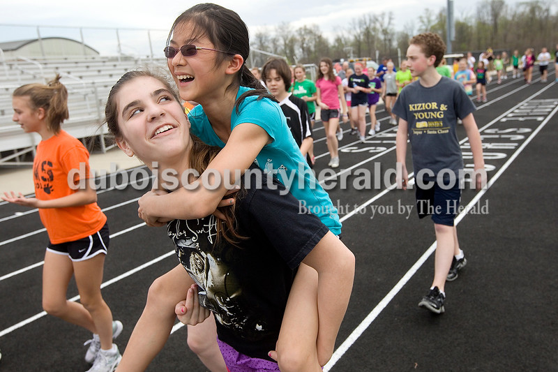 Dave Weatherwax/The Herald<br /> Jasper Middle School seventh grader Corban Bell carried her classmate Daisy Magee on her back as they walked the first lap around the track at the middle school Thursday after school. Over a hundred students spent their time after school walking 3.7 miles around the track as part of a fundraiser spearheaded by the school's Destination ImagiNation team that has been raising money to purchase Lifestraws — portable water filters that remove more than 99 percent of waterborned pathogens — to send to people in Haiti.
