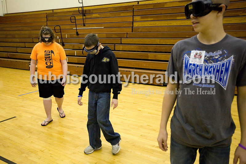 """Dave Weatherwax/The Herald<br /> Southridge Middle School seventh-graders Emily Epley, left, and Hunter Meyerholtz took slow, cautious steps as they tried to walk over to the black line in the high school gym to join their classmate Ross Eckert on Thursday morning during the middle school health fair. The students had to complete the task while wearing goggles that simulated a person's vision after they have been drinking or using drugs. The station, called """"Fatal Vision,"""" was one of several that the students were asked to visit during the fair that promoted awareness for healthy choices."""