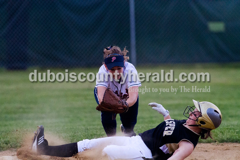 Jasper's Samantha Gerber slide safely into second base with Heritage Hills' Toni Braun attempting the tag during Tuesday nights game at Lincoln City. Heritage Hills defeated Jasper 5-4.